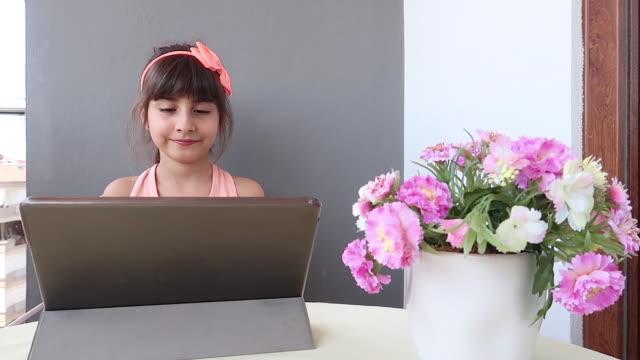 vidéos et rushes de fille de littel utilisant la tablette numérique au balcon - seulement des petites filles