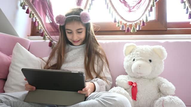 vídeos de stock e filmes b-roll de littel girl using digital tablet at home - 10 11 anos