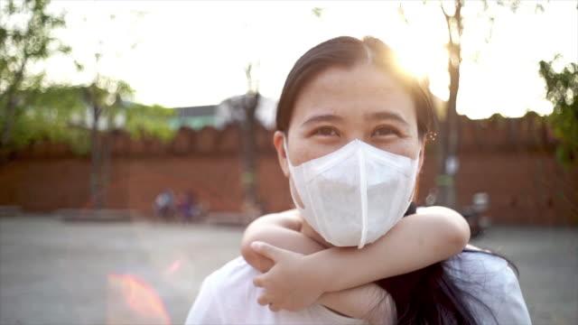 vídeos de stock, filmes e b-roll de slo mo menina litter montando as costas de sua mãe para sua mãe usar máscara facial médica para proteger germes durante a caminhada no parque público - explicar