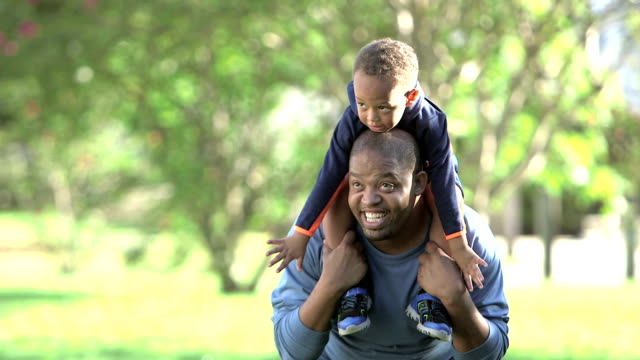 little african american boy playing on dad's shoulders - carrying on shoulders stock videos & royalty-free footage