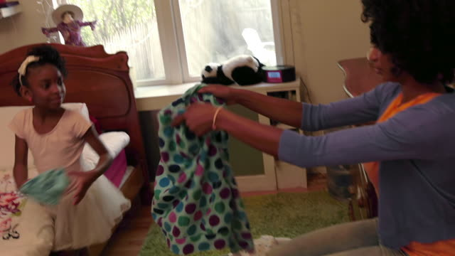 Little African American Girl Helps her mom fold Laundry in her bedroom