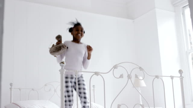 Little african girl jumping on the bed