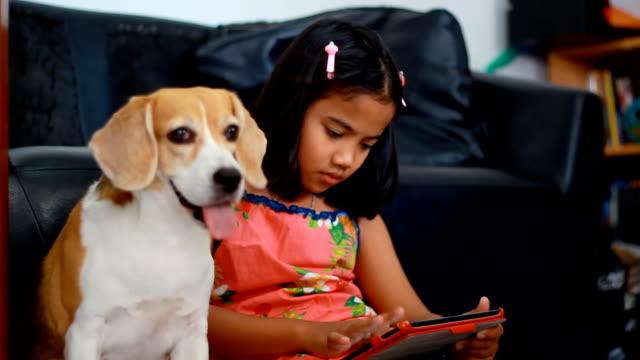 Kleine Afrikanische Mädchen mit Ihrem tablet und seine beagle-Hund auf der Suche an einem tablet arbeitet