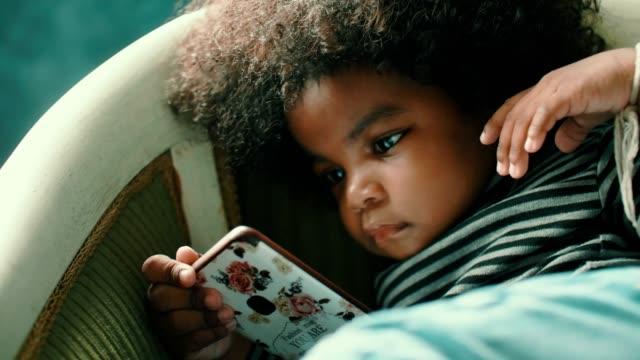 小さなアフリカの女の子(2-3歳)は、スマートフォンからビデオを見て - 孤独点の映像素材/bロール