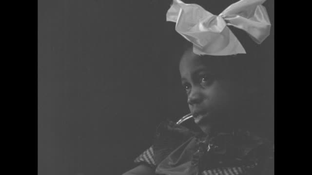 cu little africanamerican girl with big bow in hair she looks into camera / note exact day not known - hair bow stock videos & royalty-free footage