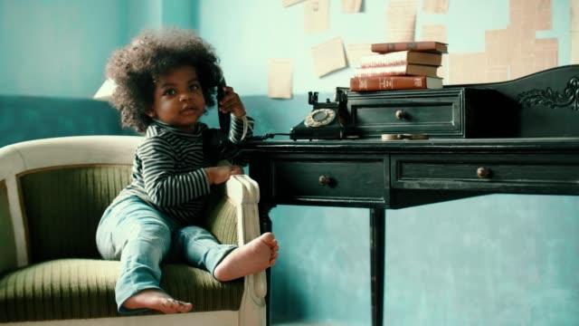 stockvideo's en b-roll-footage met weinig afro meisje (2-3 jaar) praten over roterende telefoon thuis - telefoonhoorn
