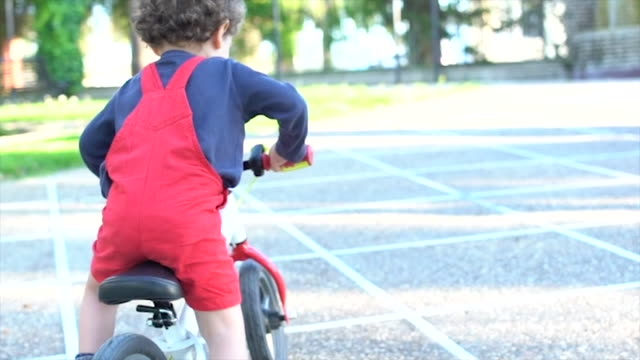 little and happy boy riding bike in park - dungarees stock videos & royalty-free footage