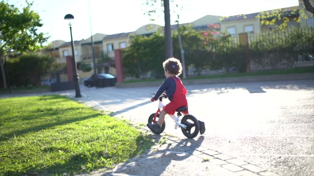 little and happy boy riding bike in park - boys stock videos & royalty-free footage