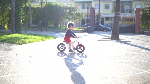 little and happy boy riding bike in park - vorschulkind stock-videos und b-roll-filmmaterial