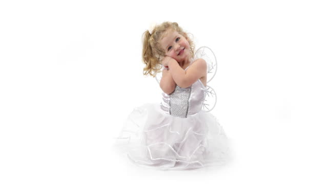 Little angel girl dressed in white angel clothes on white