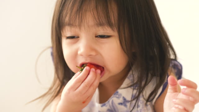 little asian baby girl is eating strawberry at her room - baby girls stock videos & royalty-free footage