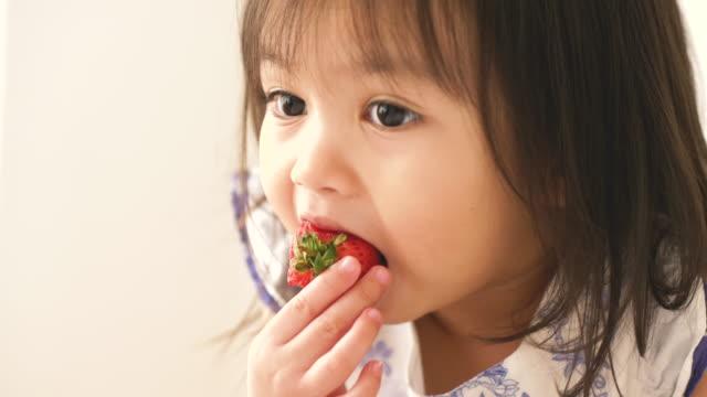 Petite fille asiatique mange fraise à sa chambre