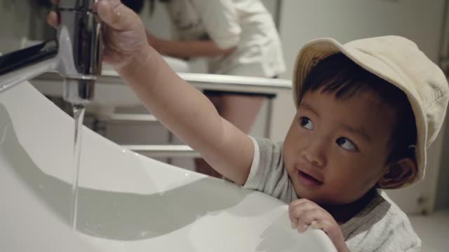 Little asian boy washing hand in bathroom.