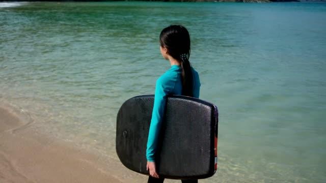 vidéos et rushes de petite fille asiatique et son body boarding à la plage. - maillot de bain