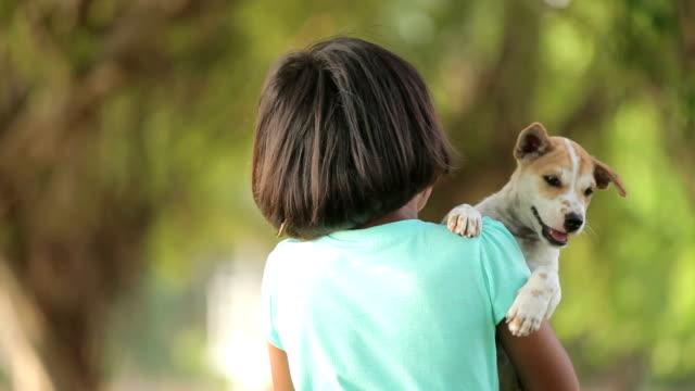 アジア少女と庭で子犬 - ペット点の映像素材/bロール