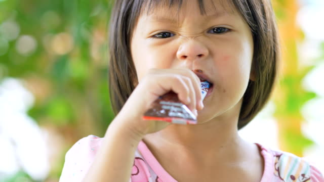 little asian girl eating snack in outdoor - spuntino video stock e b–roll