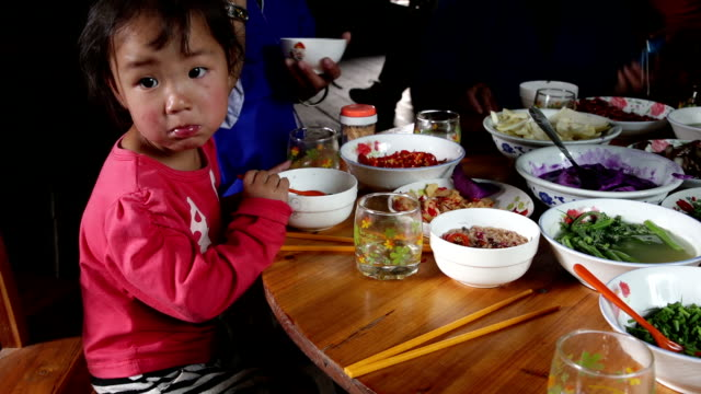 Little Asian girl eating traditional food