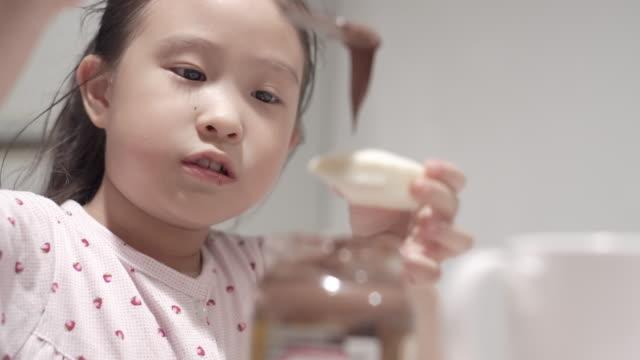 vidéos et rushes de petite fille asiatique apprécient manger le pain dans le petit déjeuner - pain