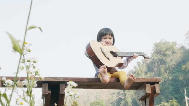 little asian girl is playing guitar with relax and leisure at the seating beside the garden - nursery school child stock videos & royalty-free footage