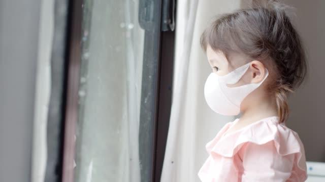 vídeos y material grabado en eventos de stock de una niña asiática o un niño pequeño que lleva máscara facial de pie junto a la puerta o ventana apuntando, golpeando y mirando afuera. - asia sudoriental