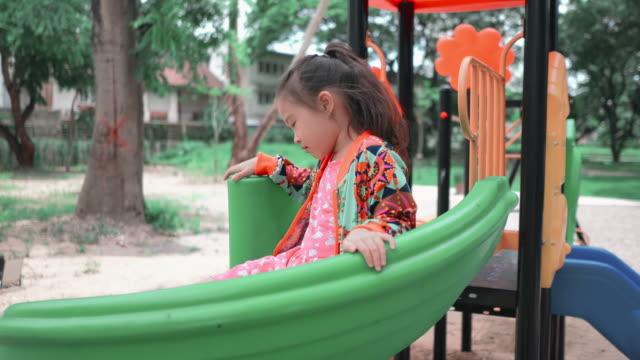 vídeos y material grabado en eventos de stock de pequeña chica asiática jugando tobogán en el patio de recreo - estructura metálica para niños