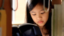 Little Asian girl reading a book in library
