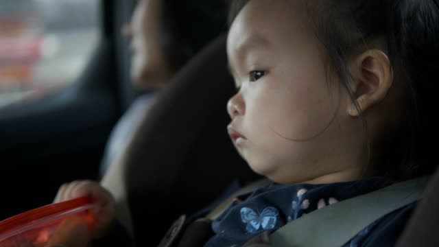 a little asian girl traveling, sitting on car sit safety ,  the beautiful child is amazed and interested in new places and the adventures that await her on that journey. - one teenage girl only stock videos & royalty-free footage