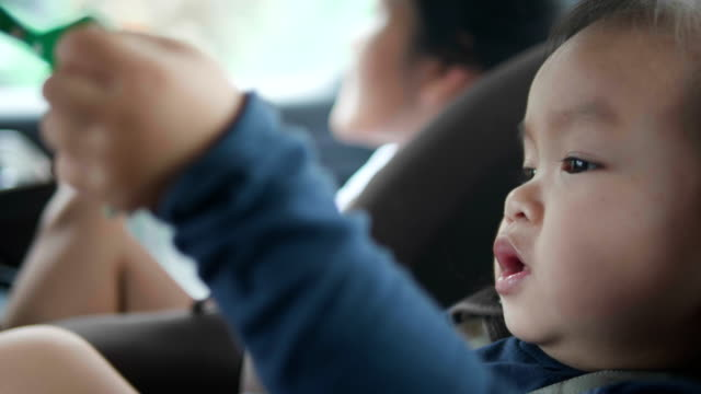 a little asian girl traveling, sitting on car sit safety , the beautiful child is amazed and interested in new places play airplane paper and the adventures that await her on that journey. - one teenage girl only stock videos & royalty-free footage