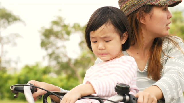 Little asian girl with boring expression is sitting on the bicycle with her mother in park