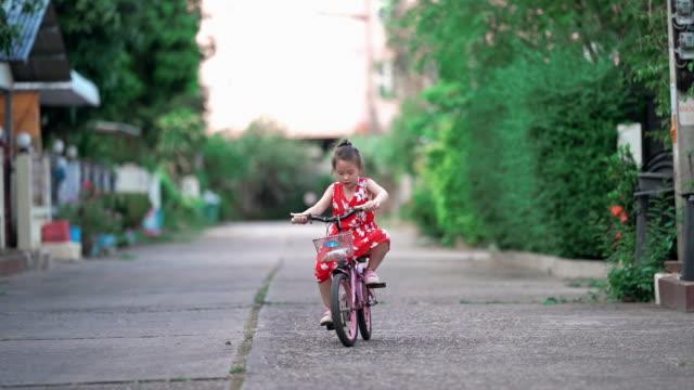 kleine asiatische mädchen lernen fahrrad zu fahren - teaching stock-videos und b-roll-filmmaterial