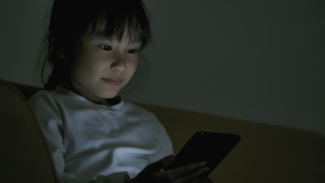 vidéos et rushes de petites filles asiatiques utilisant le smartphone la nuit. - digital tablet