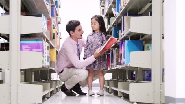 little asian students and teacher reading book in library. - school uniform stock videos and b-roll footage