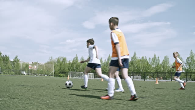 Little athletic player scoring a goal during soccer training