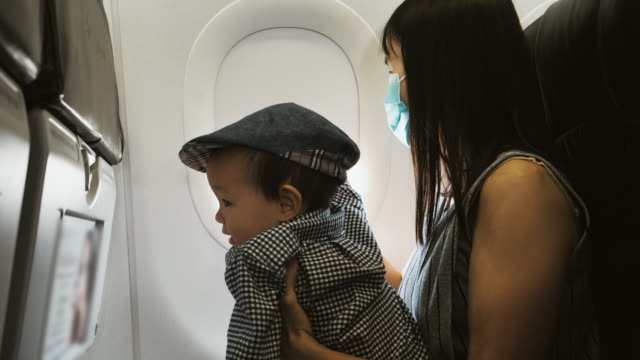 little baby boy and his mother looking out of the airplane window - 6 11 months stock videos & royalty-free footage