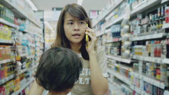 小さな男の子とお母さんはスーパーで一緒に楽しい買い物をしている、 - ショッピングカート点の映像素材/bロール