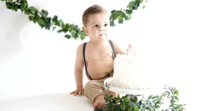スマッシュケーキパーティーで彼の最初の誕生日を祝う小さな赤ちゃんの男の子、 - 日用品点の映像素材/bロール