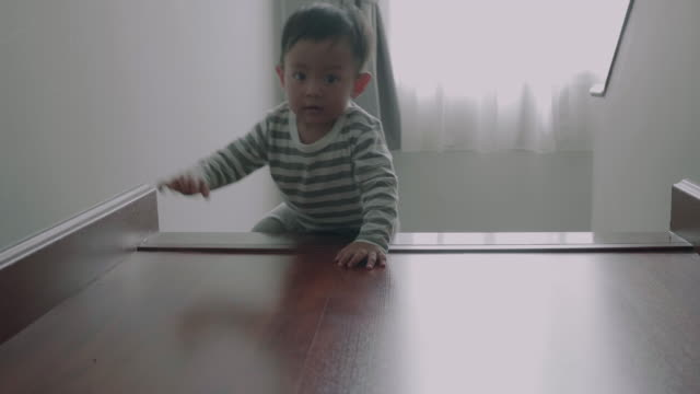 Little baby (12 months) boy climbing up the steps