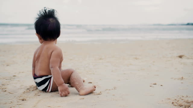 Little baby boy (6-11 months) crawling and sitting on beach.