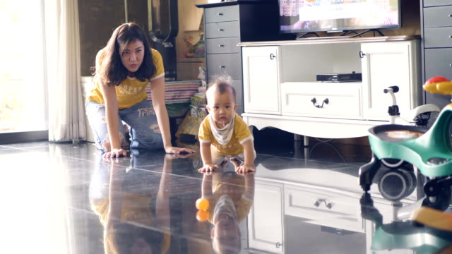 Little baby boy crawling on the floor with young mother