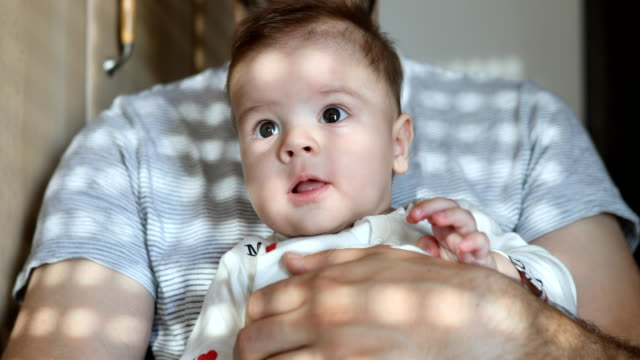 vídeos de stock e filmes b-roll de little baby boy cuddles with dad in the morning - masculinidade moderna