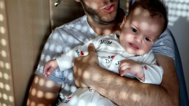 小さな男の子がお父さんと朝 cuddles します。 - ジェンダーブレンド点の映像素材/bロール