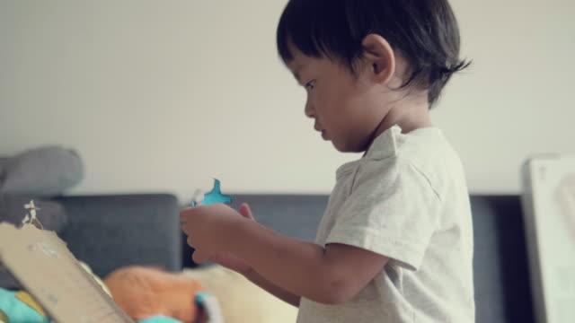 stockvideo's en b-roll-footage met baby jongetje doet kunsten en ambachten thuis - karton