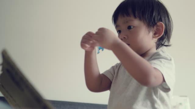 vídeos de stock e filmes b-roll de little baby boy doing arts and crafts at home - etiqueta mensagem