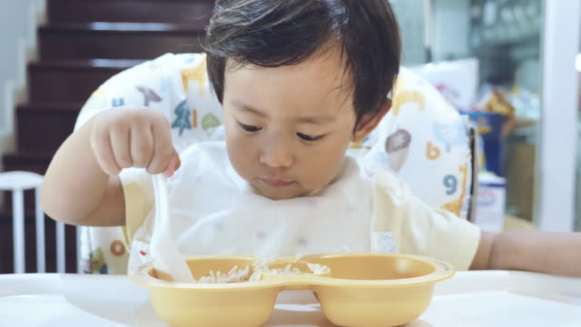 little baby boy eating baby food on high chair. - babies only stock videos & royalty-free footage