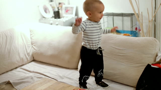 little baby boy jumping on sofa and having fun