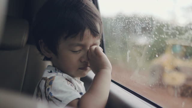 little baby boy looking out from car window - grief stock videos & royalty-free footage