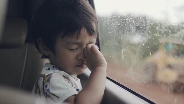 vídeos de stock e filmes b-roll de little baby boy looking out from car window - luto
