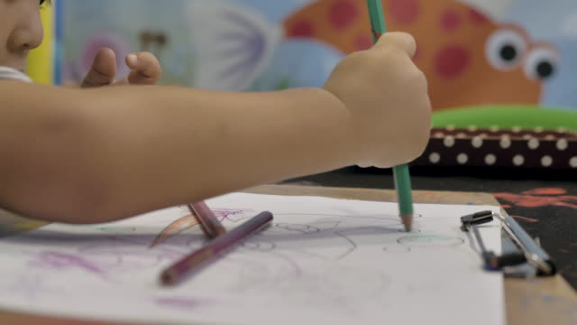Little baby boy making a drawing on the table.