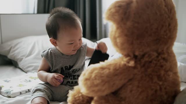 vídeos de stock, filmes e b-roll de garotinho brincando em casa com brinquedos macios de ursinho - 6 11 months