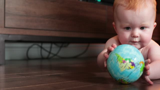 little baby boy playing with an earth shaped ball in his home - palla sportiva video stock e b–roll